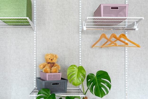 Plastic bakjes met deksel en een teddybeer op metalen planken. een moderne inloopkast in een nieuw huis