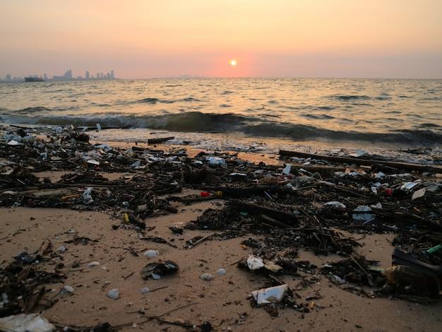 Plastic bamboeschuim en afvalvervuiling op de achtergrond van de strandzonsondergang