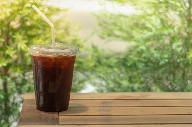 Plastic beker ijskoude zwarte koffie (americano) op houten tafel wegnemen.