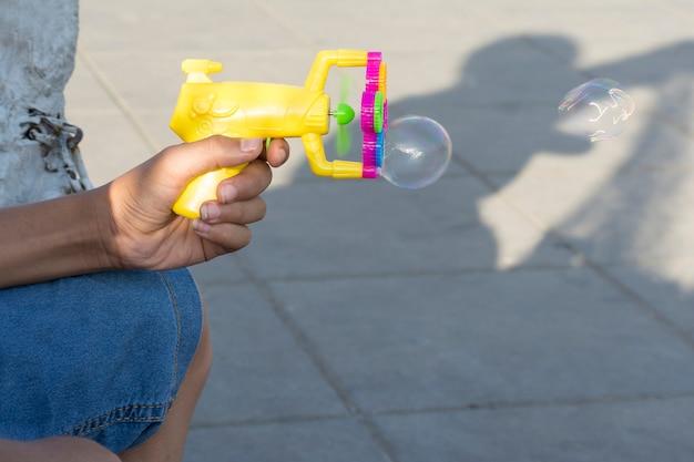 Plastic bellenmakerspistool in jonge tienerhand op openluchtgebied