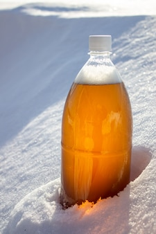 Plastic bierflesje in de sneeuw in de winter in de natuur, bierachtergrond