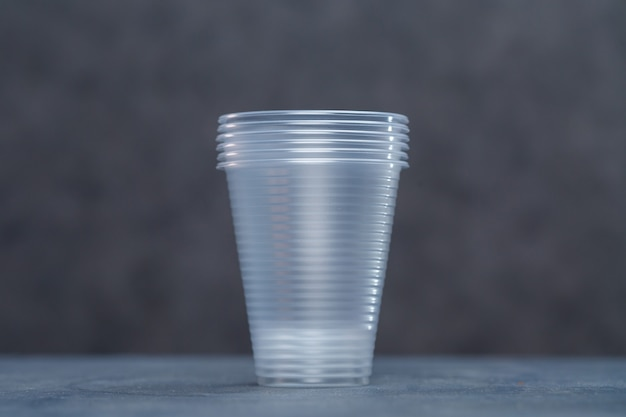 Plastic borden, wegwerpservies, borden, glazen, lepels, vorken op een grijze achtergrond. zorgen voor het milieu. het probleem is recyclen. hergebruik, veilige planeet, milieuconcept.