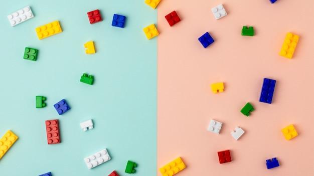 Plastic bouwstenen op blauwe en roze achtergrond