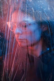 Plastic brillen. studio opname in donkere studio met neonlicht. portret van ernstige man achter het natte glas