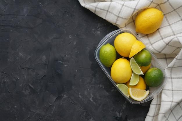 Plastic container met citroenen en limoenen op een donkere ondergrond