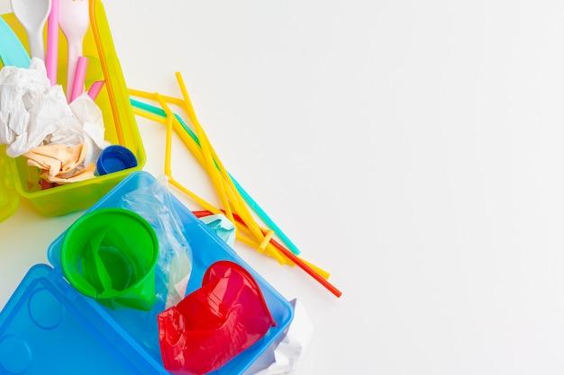 Plastic de ecologieconcept van het afvalgevaar met huisvuil en kleurrijk stro voor éénmalig gebruik, bestekkoppen, flessen op wit
