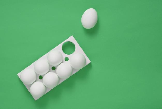 Plastic dienblad met witte eieren en op een groene pastel achtergrond