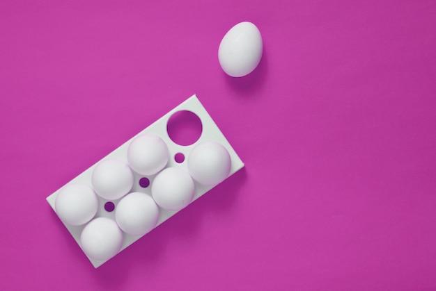 Plastic dienblad met witte eieren en op roze achtergrond
