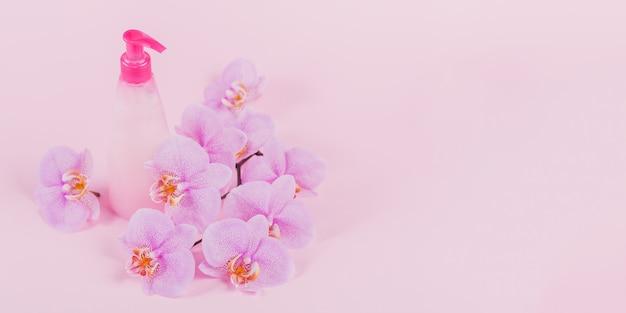Plastic dispenserfles met vloeibare cosmetische zeep, intieme was- of douchegel, paarse spons en roze orchideebloemen op lichtroze oppervlak. spa en hygiëneconcept voor vrouwen