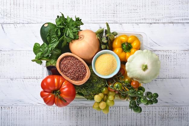 Plastic doos met assortiment van verse groenten, fruit, granen en zaden op oude houten achtergrond. veilige thuisbezorging, eten koken en gezonde, schone voedselachtergrond en mock-up.