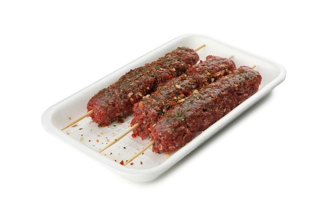 Plastic doos met rauw gehakt of lula kebab geïsoleerd op een witte tafel