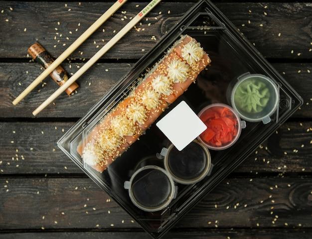 Plastic doos shushibroodjes voor levering met zalm, sauzen, wasabi, gember
