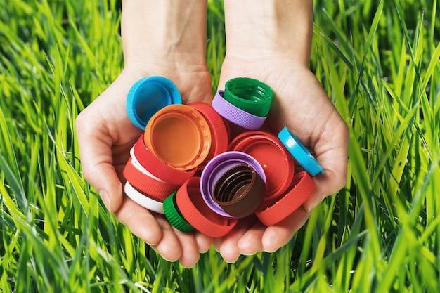 Plastic doppen van verschillende flessen in handen op gras