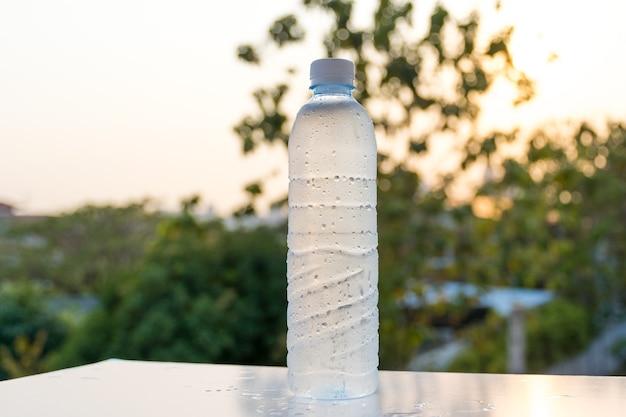 Plastic drinkwaterfles met mooie zonlichtachtergrond