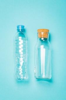Plastic en glazen flessen voor water op een blauwe achtergrond, een alternatief