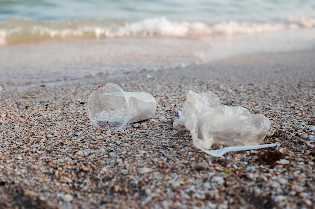 Plastic en plastic zak, afval op de achtergrond van een zandstrand.
