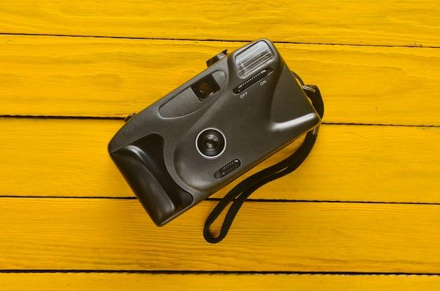 Plastic filmcamera op een gele houten tafel. hipster lomography.
