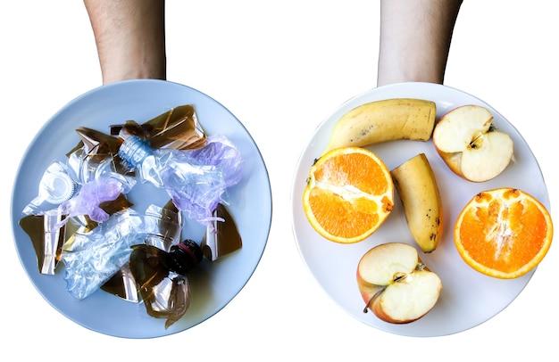 Plastic fles en fruit op de plaat. mensen die vervuild voedsel eten. omgevingsprobleem. ecologische ramp. recycling probleem. keuze.