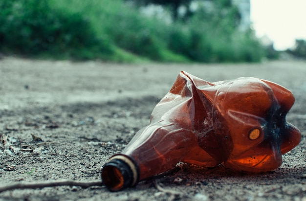 Plastic fles in het bos dichtbij de vijver. milieuvervuiling. milieukwestie en rampspoed.
