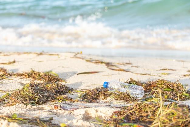 Plastic fles met dop gewassen upbeach gemengd met zeewier