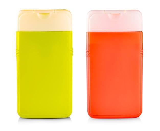 Plastic fles met shampoo of hygiënisch cosmetisch product op wit wordt geïsoleerd