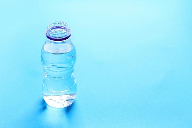 Plastic fles met water op blauw.