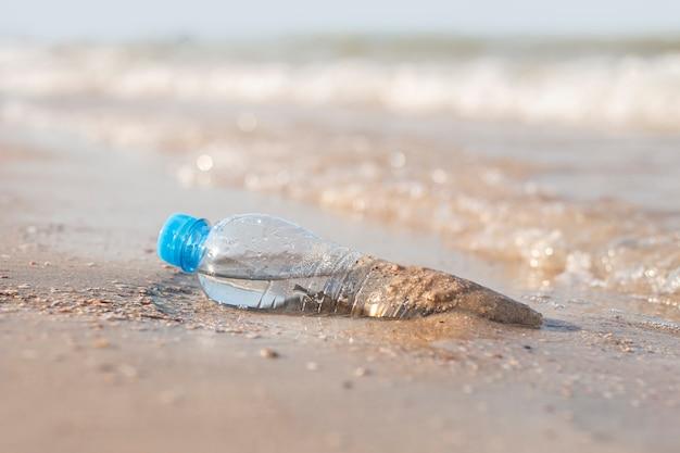 Plastic fles met water op de achtergrond van een zandstrand op een zonnige dag.