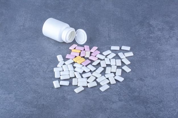 Plastic fles omgevallen naast een stapel kauwgom op marmeren oppervlak