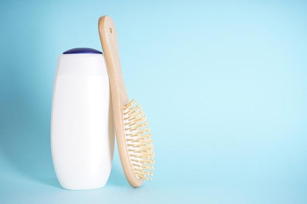 Plastic fles voor lichaamsverzorging en een houten haarborstel op een blauwe achtergrond. ruimte voor tekst.