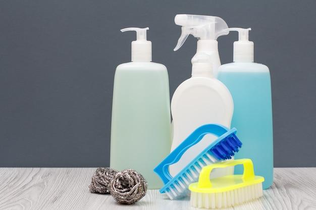 Plastic flessen afwasmiddel, glas- en tegelreiniger, wasmiddel voor magnetrons en fornuizen, borstels en metalen sponzen op grijze achtergrond. was- en schoonmaakconcept.