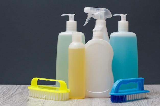 Plastic flessen afwasmiddel, glas- en tegelreiniger, wasmiddel voor magnetrons en fornuizen, borstels op grijze achtergrond. was- en schoonmaakconcept.
