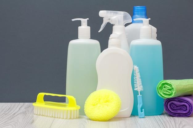 Plastic flessen afwasmiddel, glas- en tegelreiniger, wasmiddel voor magnetrons en fornuizen, borstels, sponzen en vuilniszakken op grijze achtergrond. was- en schoonmaakconcept.
