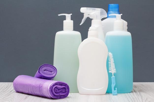 Plastic flessen afwasmiddel, glas- en tegelreiniger, wasmiddel voor magnetrons en fornuizen en vuilniszakken op grijze achtergrond. was- en schoonmaakconcept.