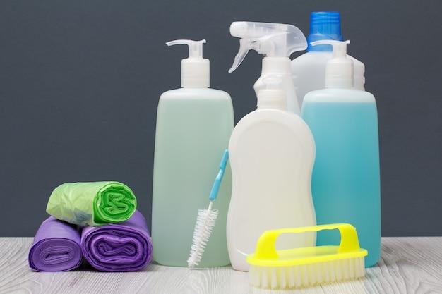 Plastic flessen afwasmiddel, glas- en tegelreiniger, wasmiddel voor magnetrons en fornuizen, vuilniszakken en borstels op grijze achtergrond. was- en schoonmaakconcept.