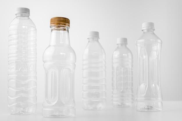 Plastic flessen in verschillende vormen en maten op witte tafel en achtergrond