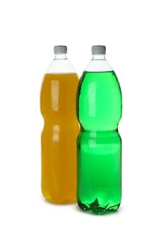 Plastic flessen met groene en oranje frisdrank geïsoleerd op een witte ondergrond
