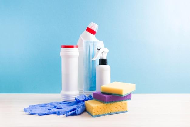 Plastic flessen met schoonmaakproducten en schoonmaaksponzen, rubberen wegwerphandschoenen en een beschermend stoffen masker op een blauwe ondergrond