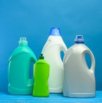 Plastic flessen met wasmiddelen op blauwe achtergrond, close-up