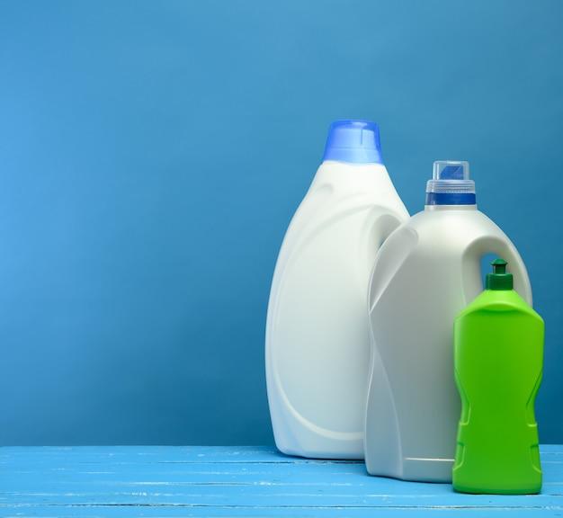 Plastic flessen met wasmiddelen op blauwe achtergrond, exemplaarruimte