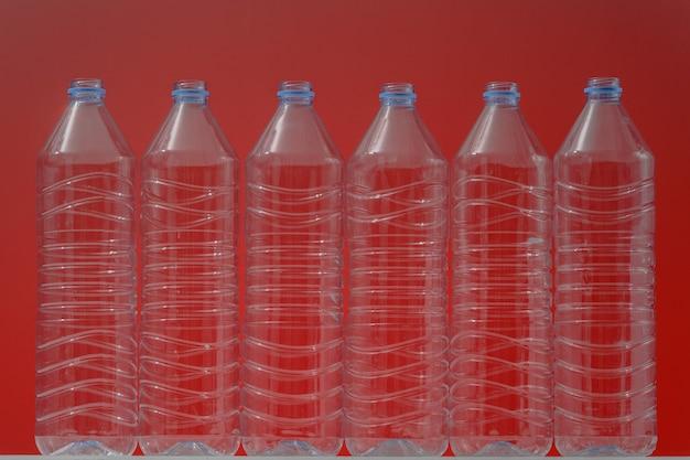 Plastic flessen op een rode achtergrond als symbool van ecologische rampen. lege flessen uit water als reclame voor recycling.