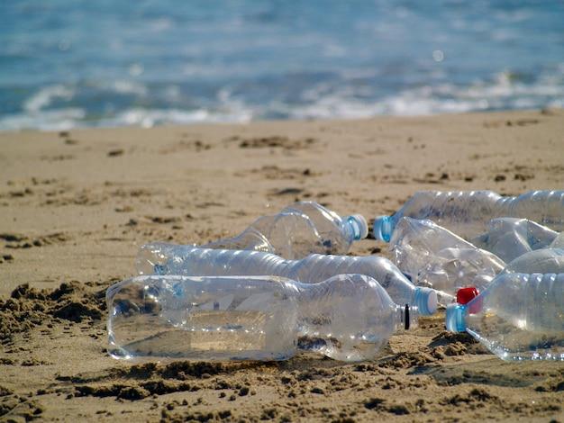Plastic flessen op het strand, recyclen, verminderen en hergebruiken