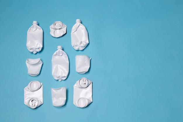 Plastic flessen uit het huisvuil staan op een blauwe muur met kopie ruimte. concept van verstopping van natuurlijke hulpbronnen en verwerking van plastic producten. .