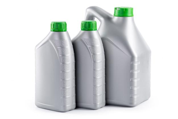 Plastic flessen van automobiele oliën die op een wit worden geïsoleerd