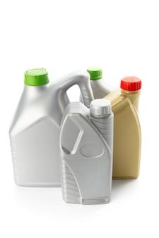 Plastic flessen van automobiele oliën die op wit worden geïsoleerd
