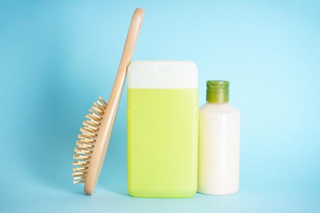Plastic flessen voor lichaamsverzorging en een houten haarborstel op blauwe achtergrond.