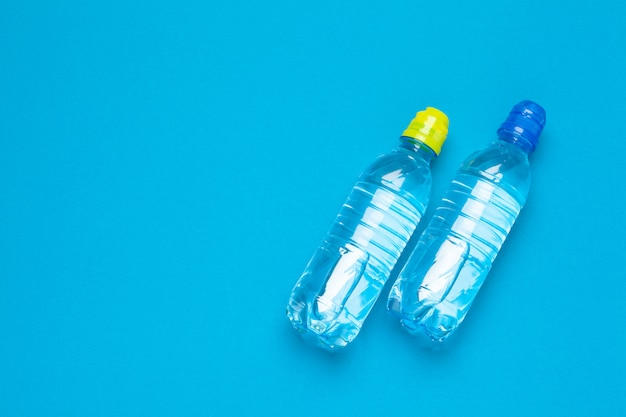 Plastic flessen water met doppen van verschillende kleur op de tafel
