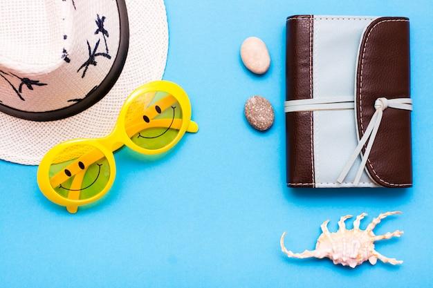 Plastic gele zonnebril met geschilderde ogen en een glimlach op de bril, hoed, notitieboekje, stenen en een schelp