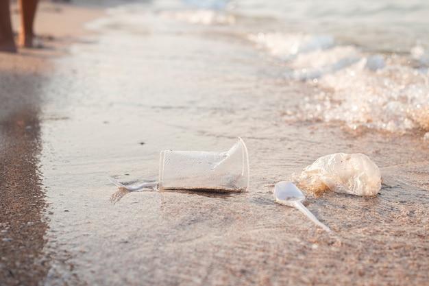 Plastic gerechten en een plastic zak op de achtergrond van een zandstrand.