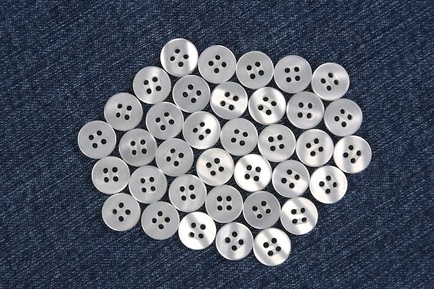 Plastic glanzende knopen voor kleding op een stoffenachtergrond. mode en kleding. fabrieksindustrie