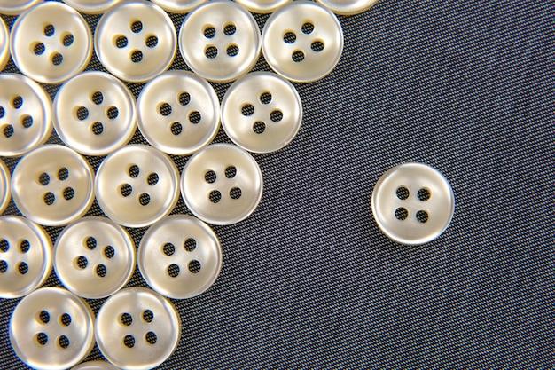 Plastic glanzende knopen voor kleding op een stoffenachtergrond. mode en kleding. fabrieksindustrie.